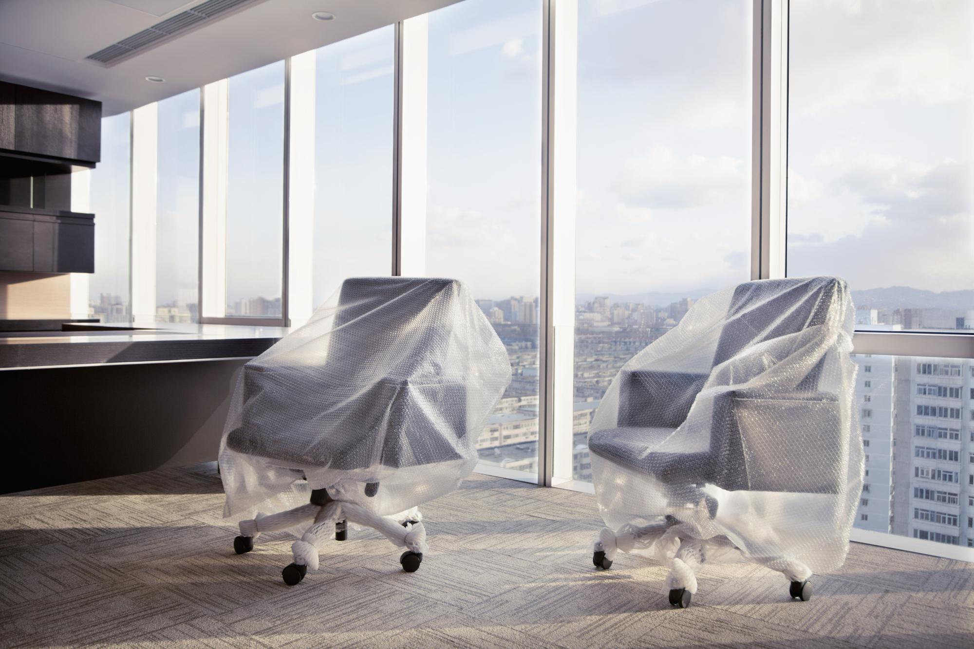 in Luftpolsterfolie gehüllte Bürostühle